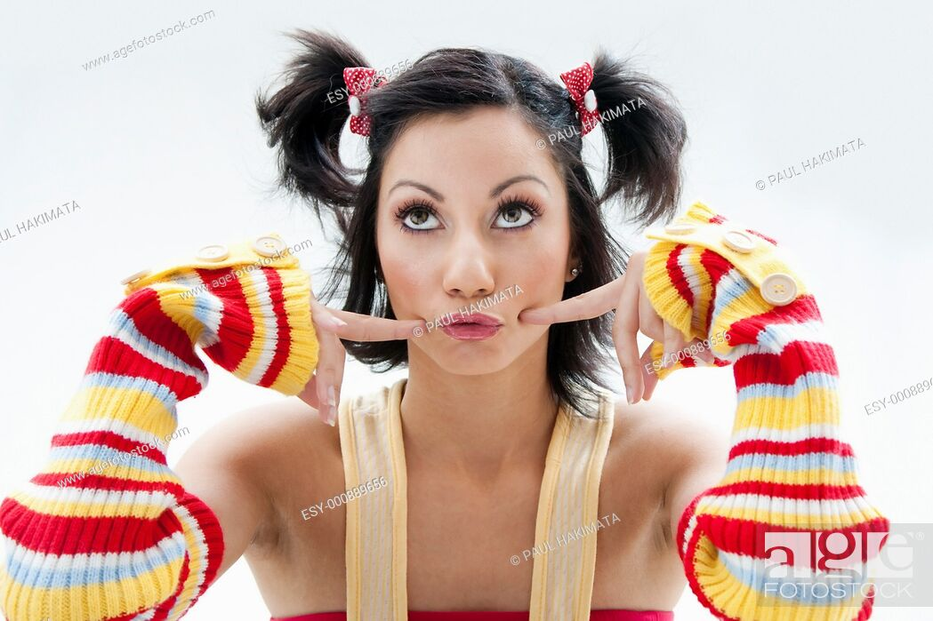 Stock Photo: Beautiful fun latina girl with bright colored arm warmers and ponytails with red ribbons in her hair looking up, isolated.