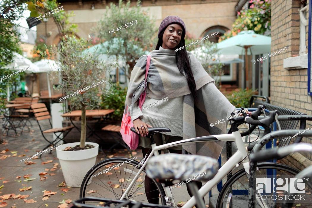 Photo de stock: Portrait confident young woman with bicycle on cafe patio.
