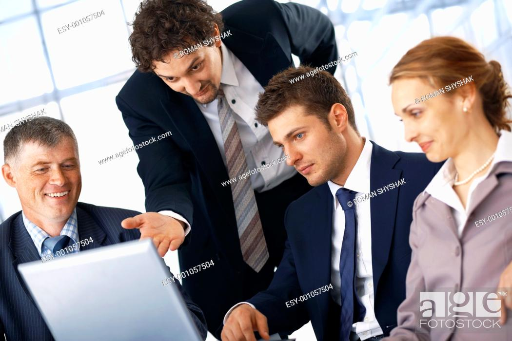 Stock Photo: Business man showing something on laptop to his colleagues.