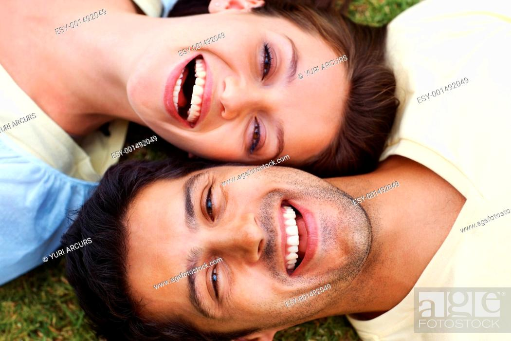 Stock Photo: Closeup portrait of beautiful young couple lying on grass.