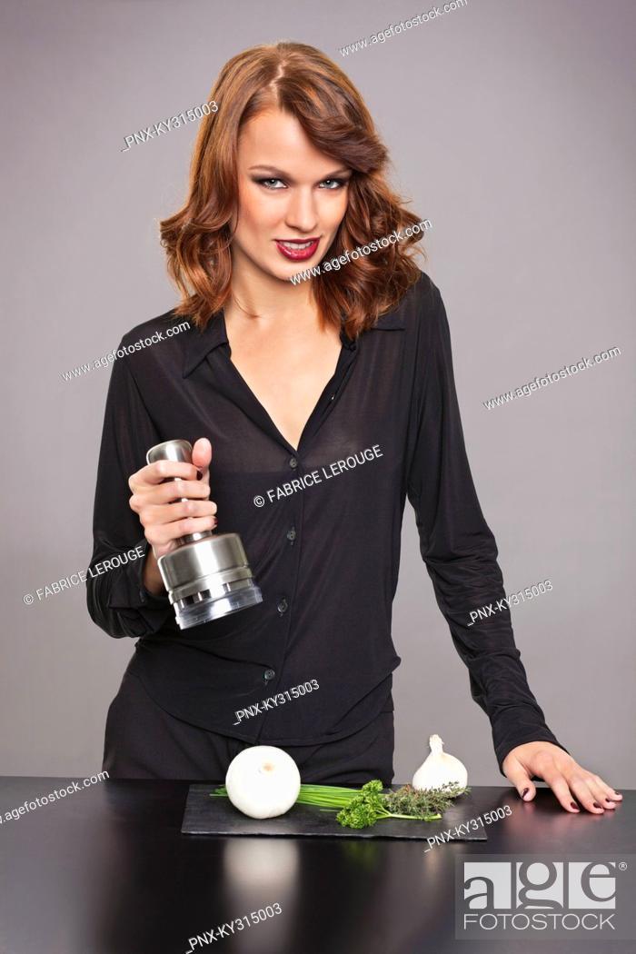 Stock Photo: Young woman using onion chopper.