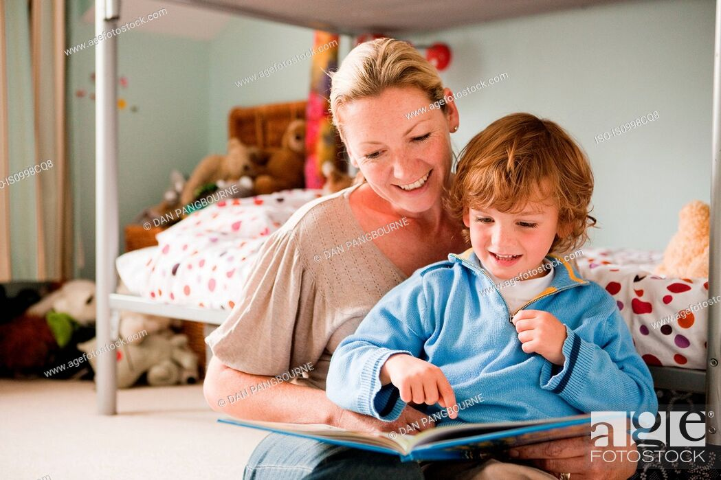 Stock Photo: Mother reading a book with her son in his bedroom.