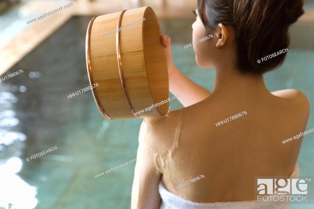 Stock Photo: Woman pouring water on her shoulder with wooden tub, rear view, Japan.