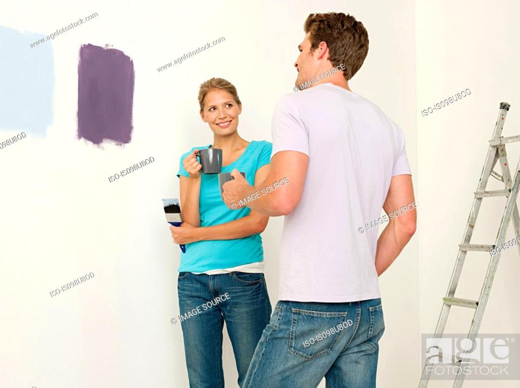 Stock Photo: Young couple looking at paint on wall.
