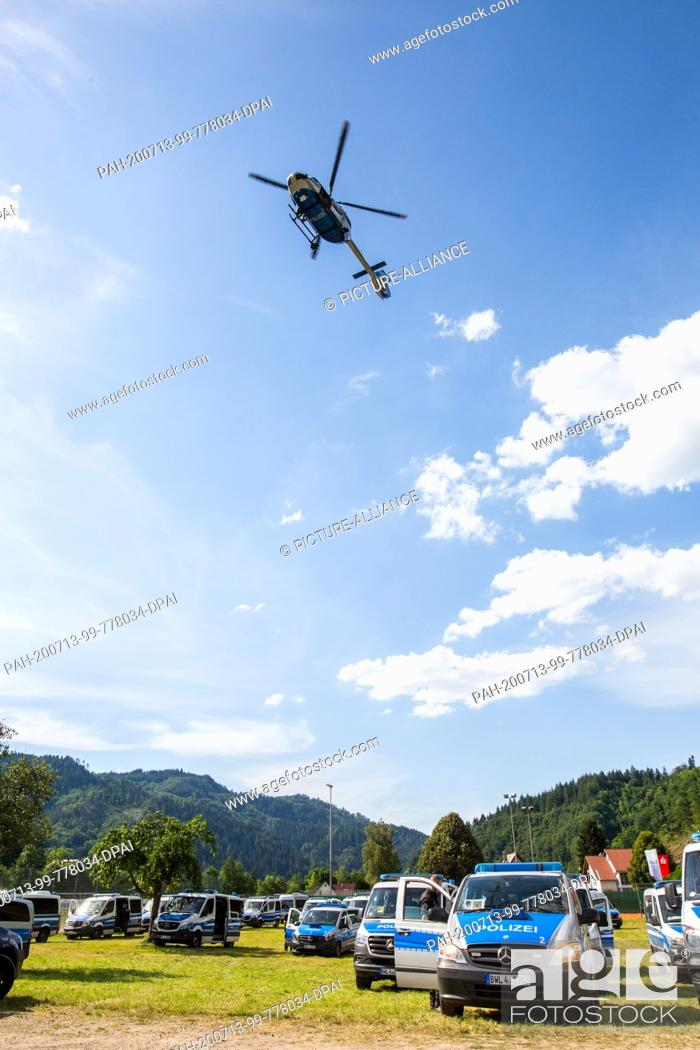 Stock Photo: 13 July 2020, Baden-Wuerttemberg, Oppenau: A police helicopter flies over a sports field near the community of Oppenau, where police vehicles are parked and.