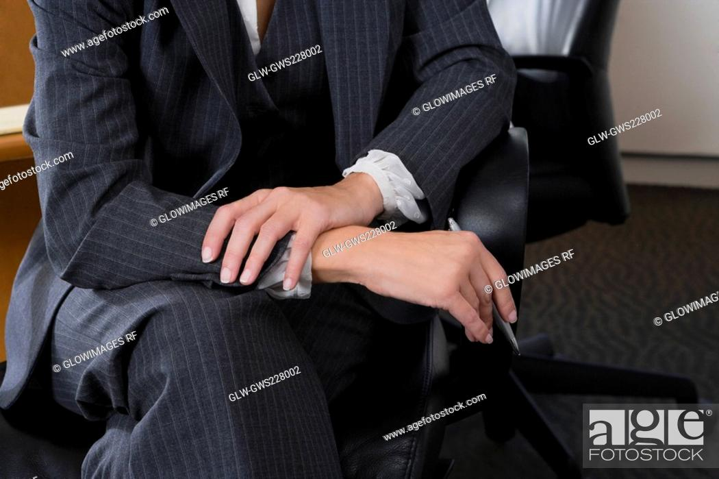 Stock Photo: Mid section view of a businesswoman sitting on a chair.