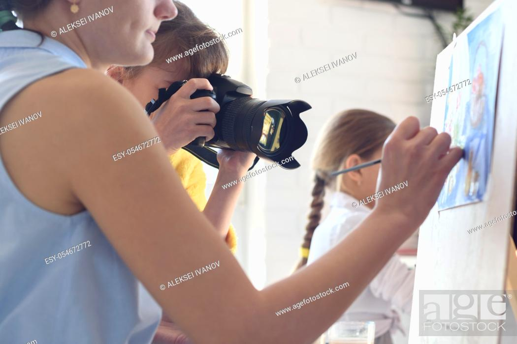Stock Photo: Girl takes pictures of how the artist works.