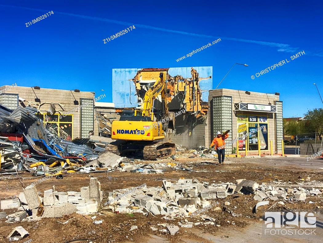 Imagen: Demolition of a store building by a tracked vehicle in downtown Tucson Arizona.