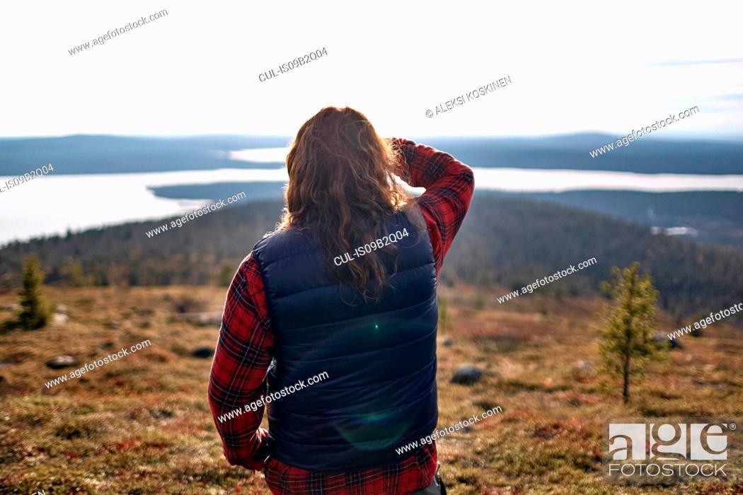 Photo de stock: Hiker looking out to lake, Keimiotunturi, Lapland, Finland.