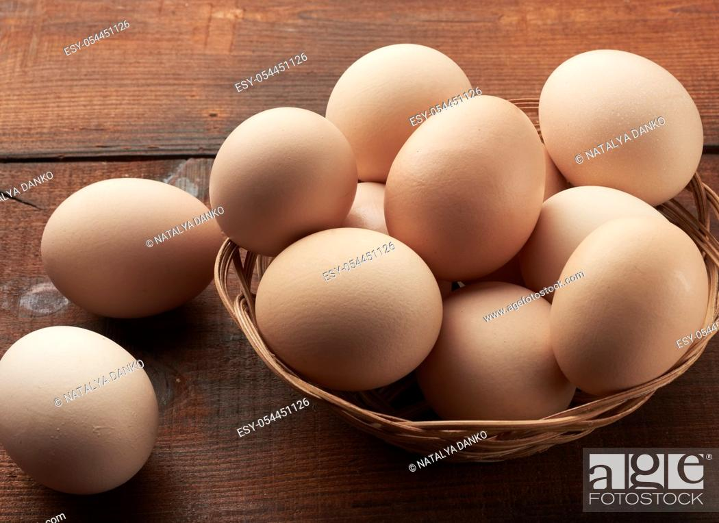 Stock Photo: raw brown chicken eggs in a wooden plate on the table, top view.
