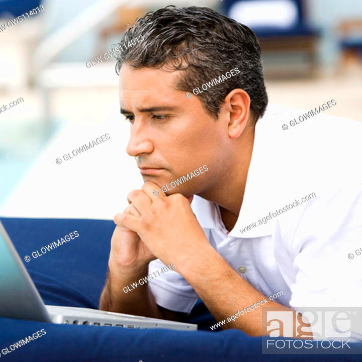 Stock Photo: Close-up of a mid adult man lying down in front of a laptop.