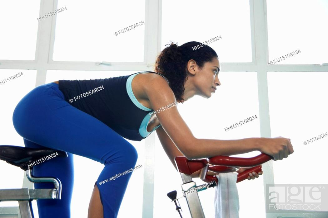 Stock Photo: Young woman indoor cycling (low angle view).