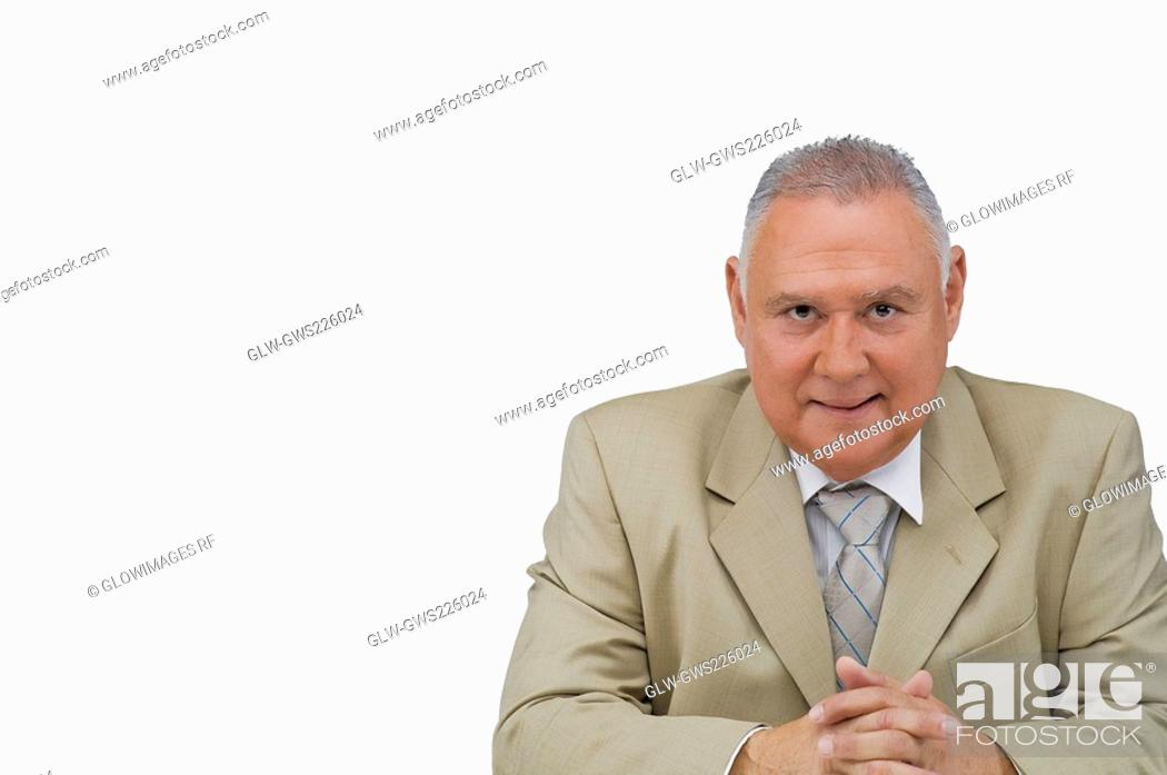 Stock Photo: Portrait of a businessman sitting with his hands clasped.