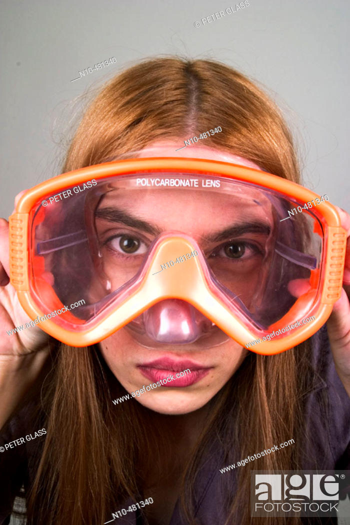 Stock Photo: Young woman, with long red hair, looking through a pair of swimming goggles.