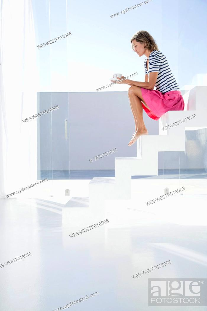 Stock Photo: Spain, Mid adult woman sitting on stairway with cup.