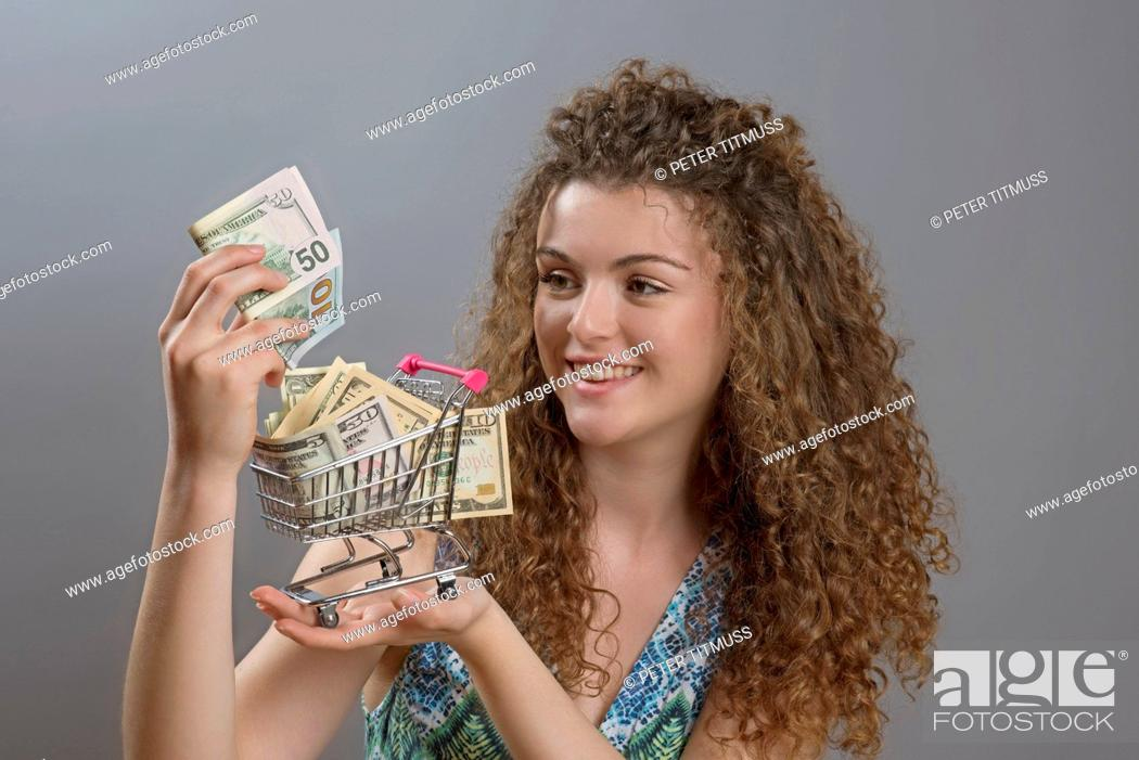 Stock Photo: Concept of the cost of living a smiling woman holding supermarket trolley full of cash.