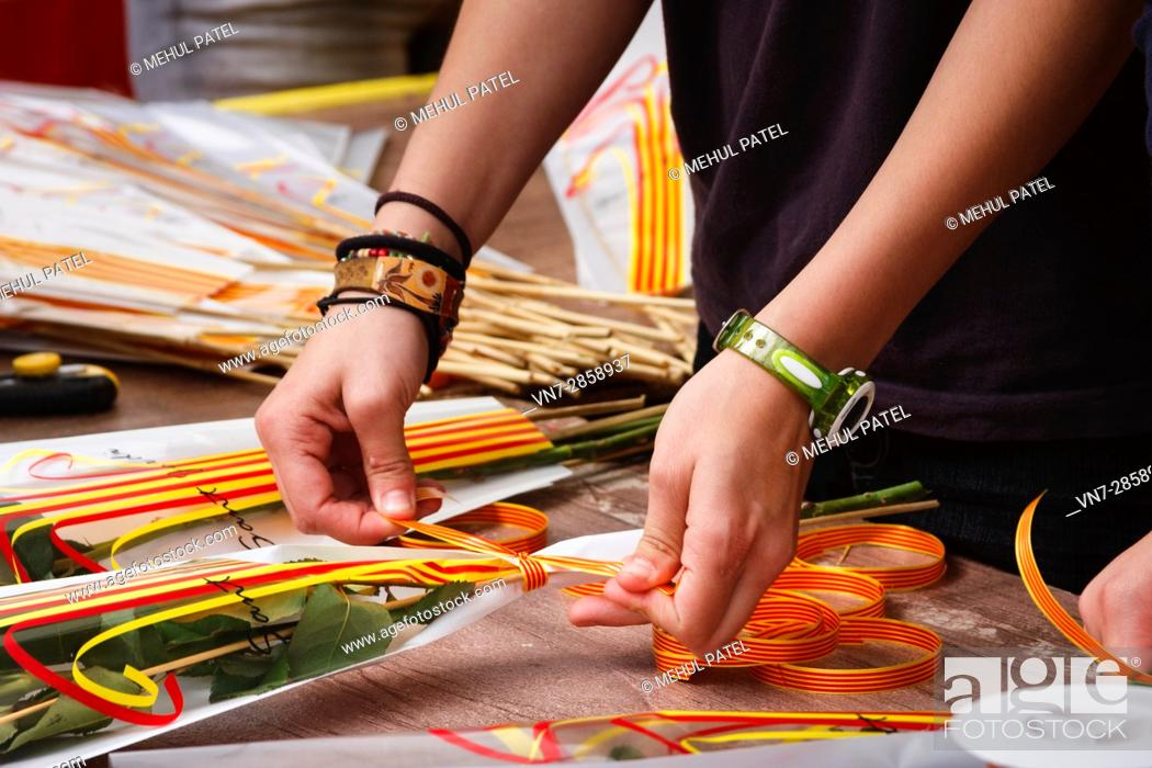 Stock Photo: Ribbons with the Catalan colours being tied to a rose bouquet on the day Sant Jordi (April23) in Tarragona, Catalonia, Spain.