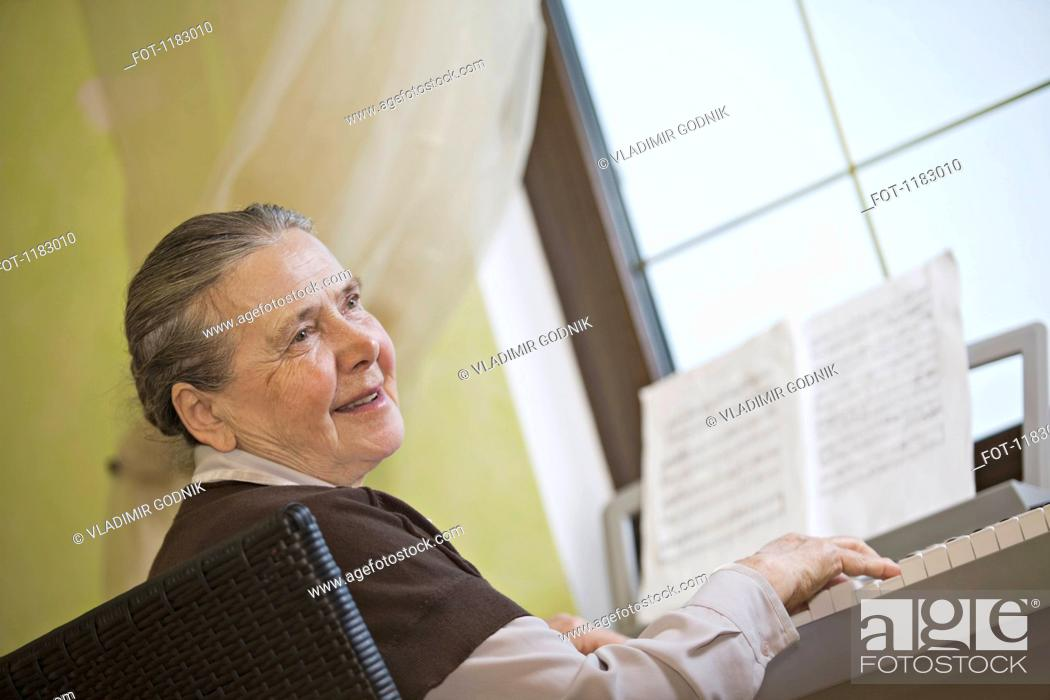 Stock Photo: A cheerful senior woman playing an upright piano.