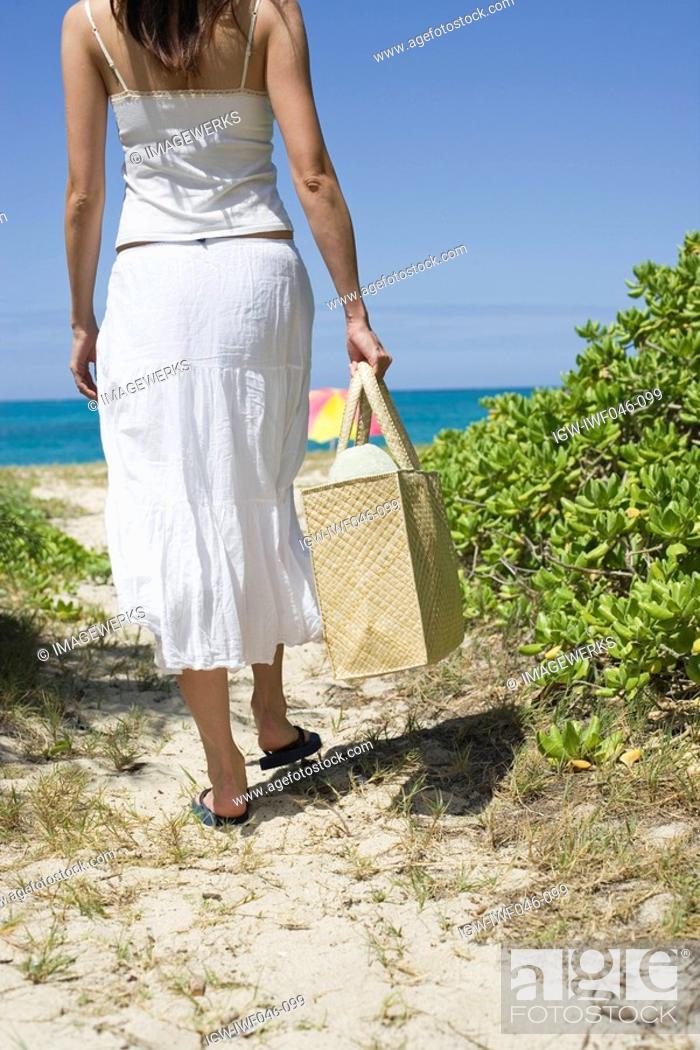 Stock Photo: Rear view of a woman walking towards beach.