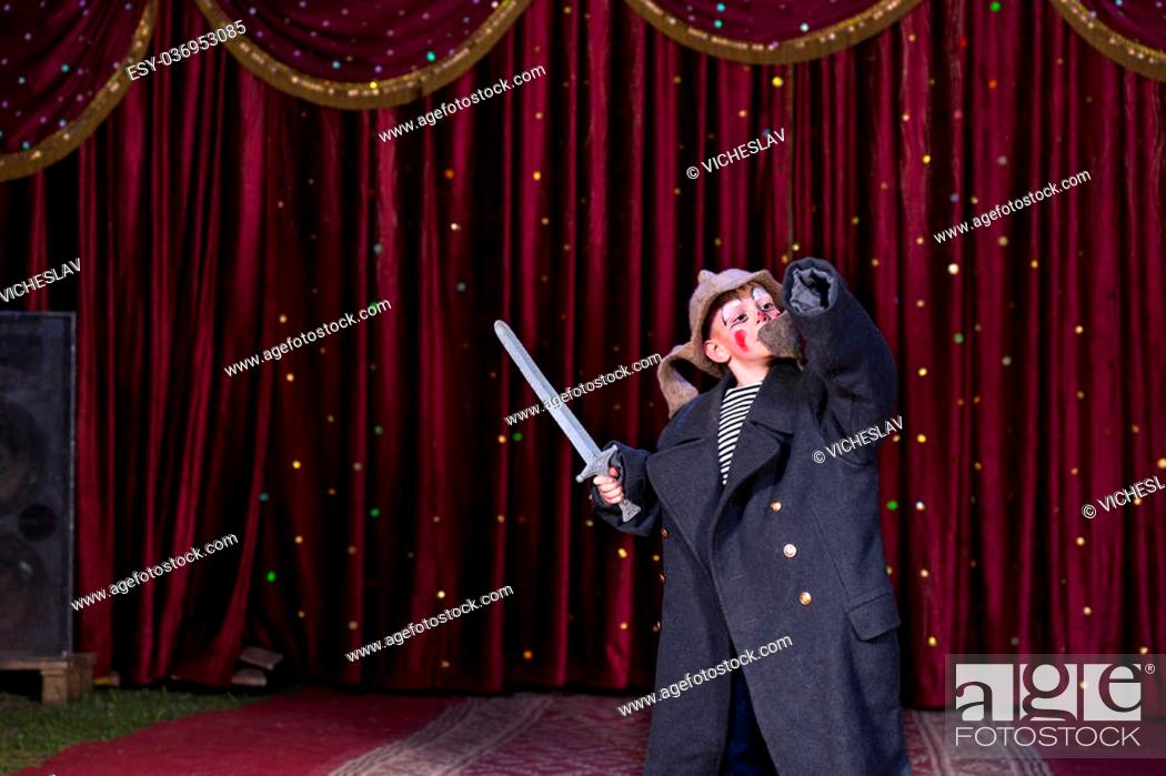 Stock Photo: Young Boy Wearing Clown Make Up and Over Sized Coat Holding Toy Prop Sword with Arm Raised Standing on Stage with Red Curtain.