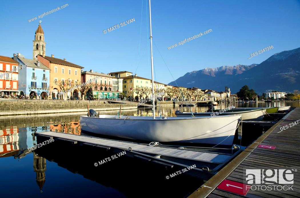 Stock Photo: Boats mooring along docks in Lake Maggiore with buildings and the Swiss Alps in the background; Ascona, Ticino, Switzerland.