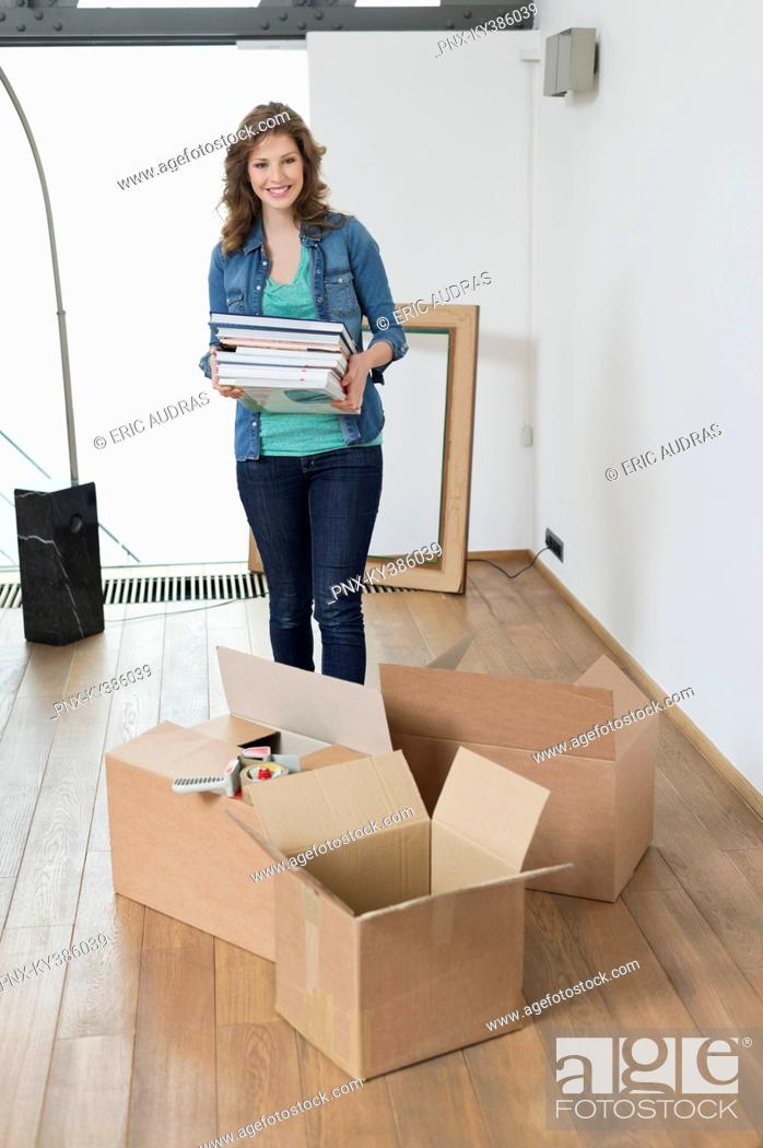 Stock Photo: Woman carrying stack of magazines.