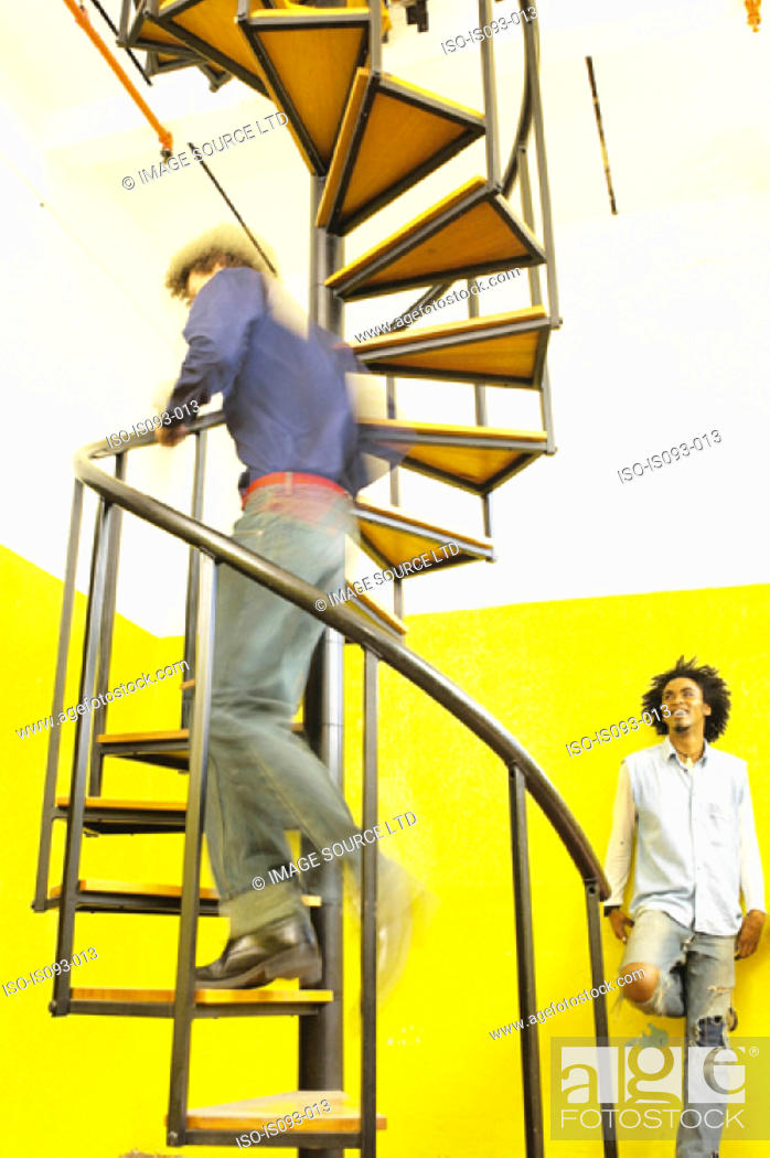 Stock Photo: Man going up spiral stairs.
