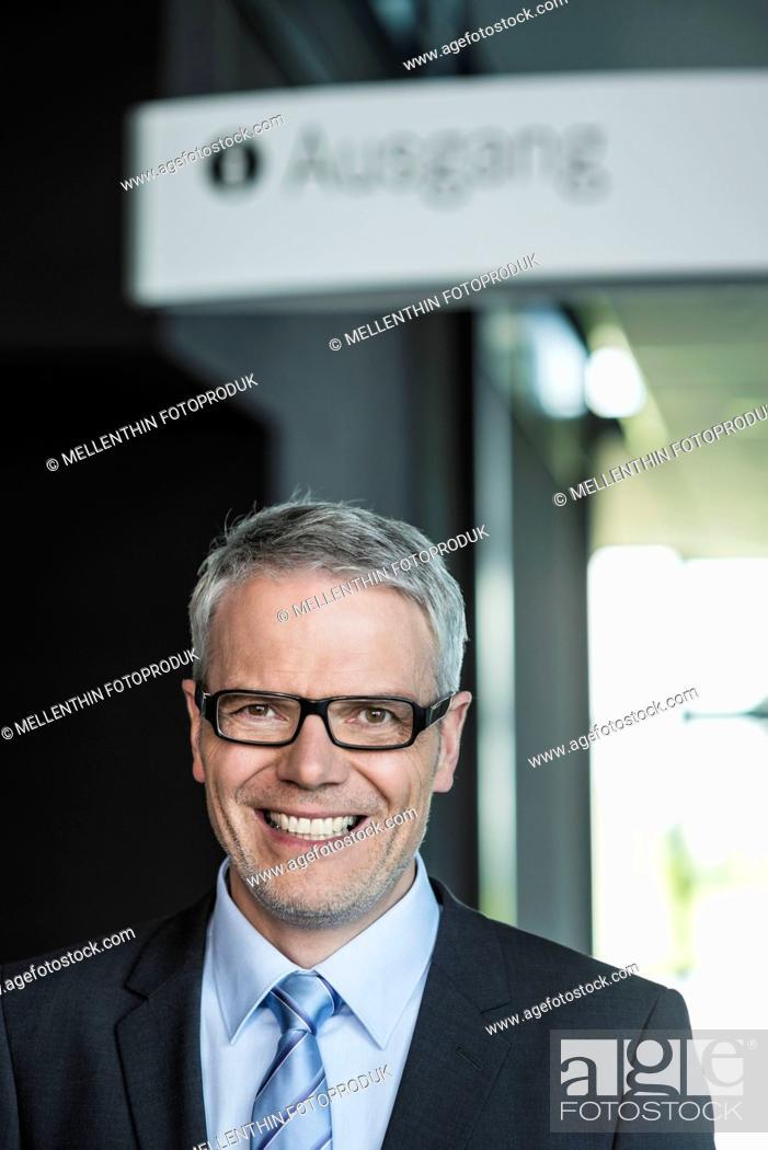 Stock Photo: Germany, Stuttgart, Businessman standing in office building, portrait, smiling.