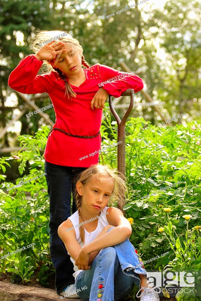 Stock Photo: Two girls resting from garden work.