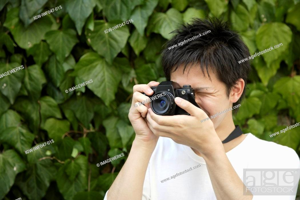 Stock Photo: Portrait of a young man photographing.