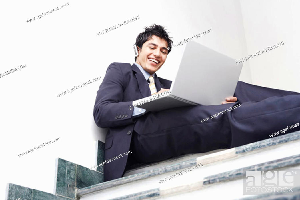 Stock Photo: Low angle view of a businessman sitting on the staircase and using a laptop.