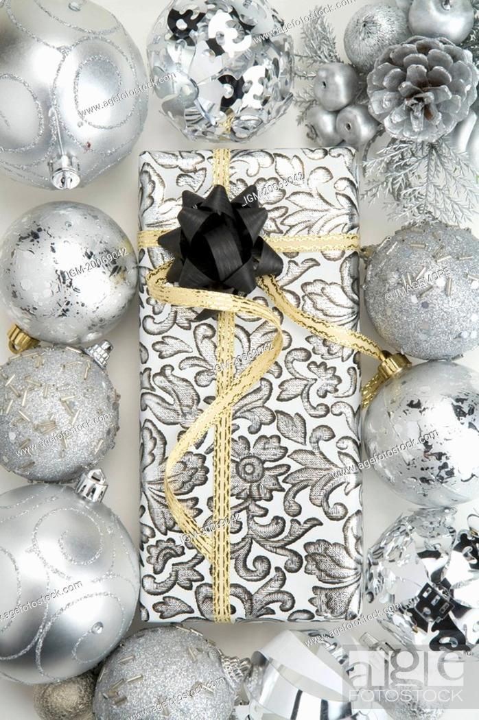 Stock Photo: Christmas baubles around a packed gift with ribbon.