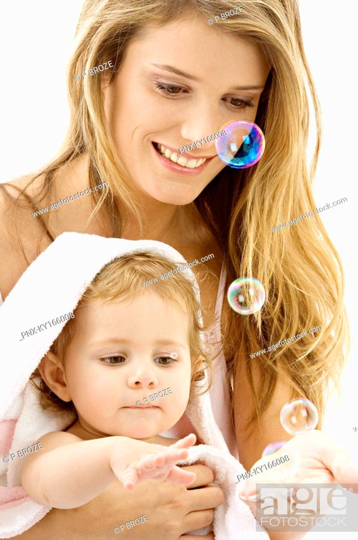 Stock Photo: Close-up of a young woman and her son playing with soap bubbles.