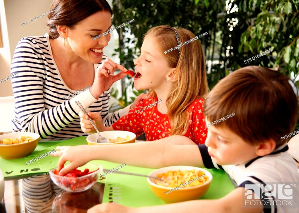 Stock Photo: Mother and children eating breakfast.