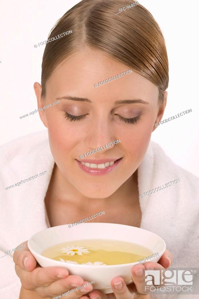 Stock Photo: Woman with white towel and bowl of tea.