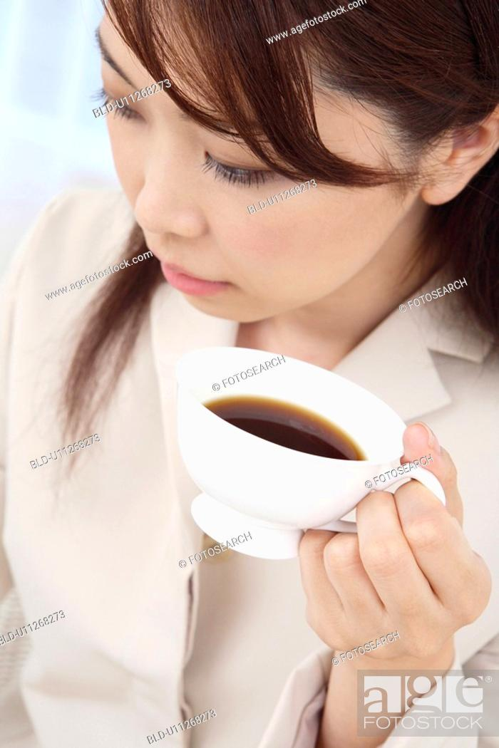 Stock Photo: Woman holding coffee in one hand.