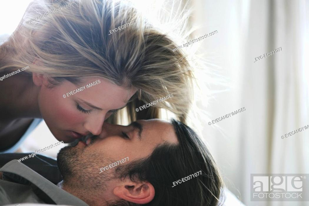 Stock Photo: Young couple kissing in bed.