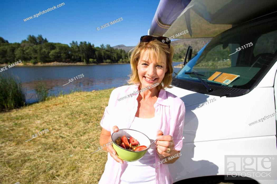 Stock Photo: Mature woman with breakfast bowl by motor home and lake, smiling, portrait.