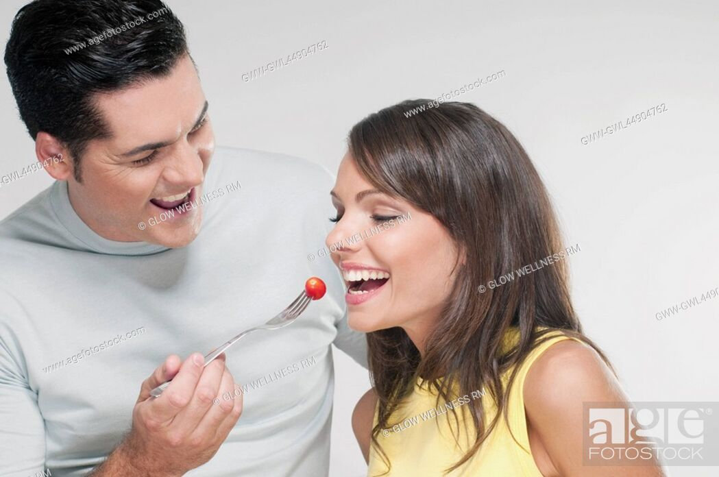 Imagen: Man feeding woman a cherry tomato.