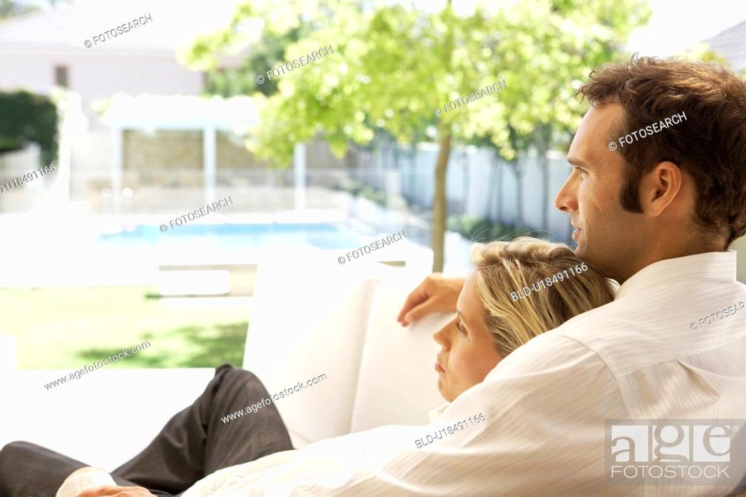 Stock Photo: Mid adult couple relaxing on sofa and looking at garden.