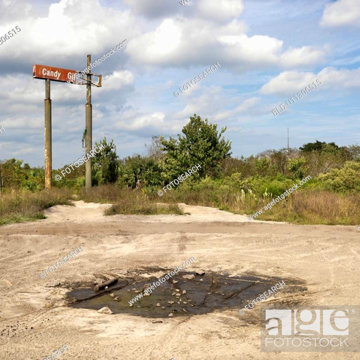 Stock Photo: Old sign in rural setting with mud puddle in foreground.