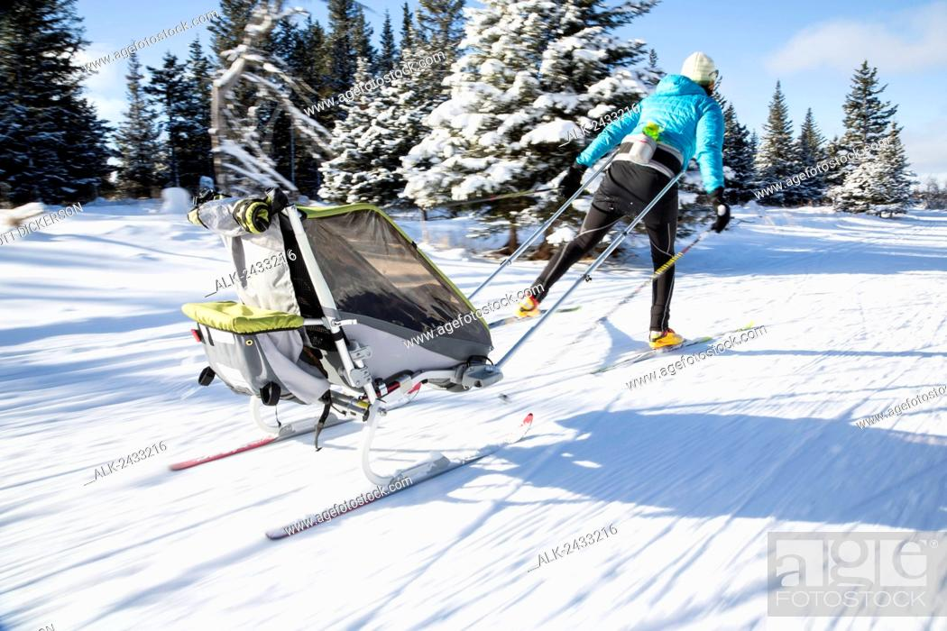 Mother cross country skiing with a baby riding in a ski sled