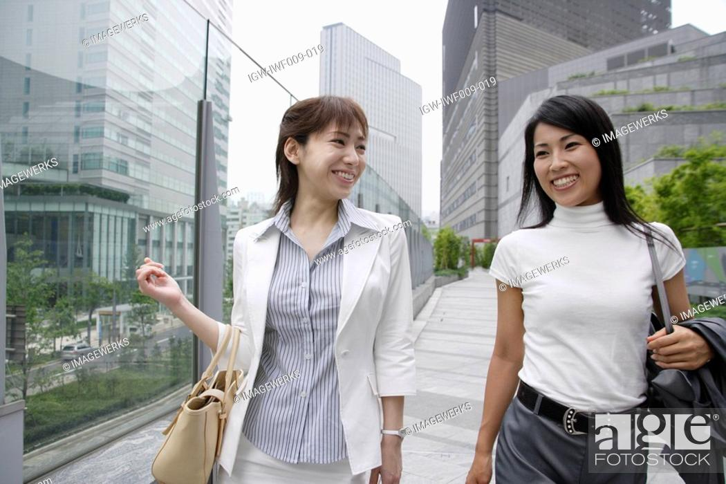 Stock Photo: Two women shares a joke walking beside the glass railing.