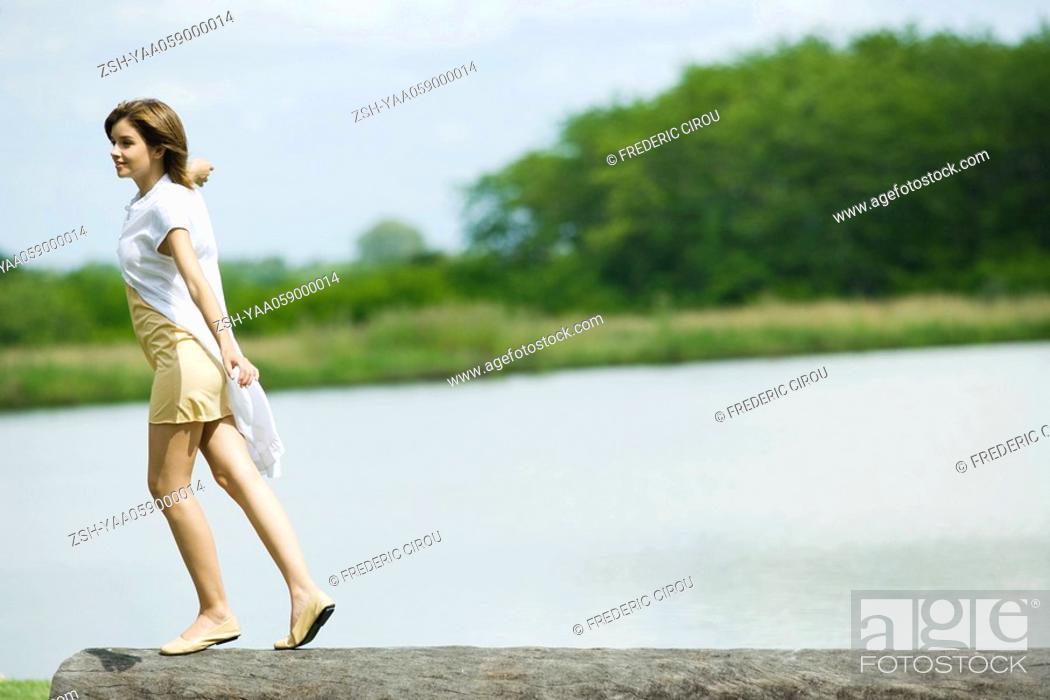 Stock Photo: Young woman walking along top of log.