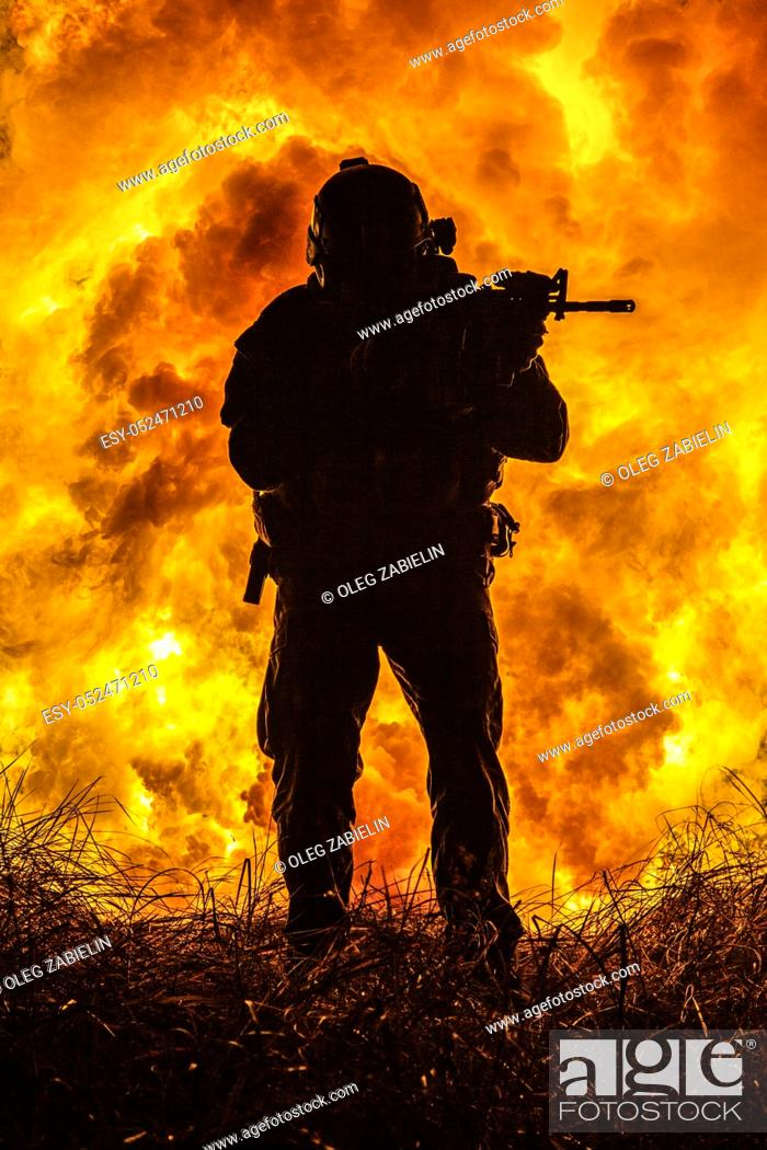 Imagen: Backlit silhouette of special forces marine operator in forest on fire explosion background. Battle, bombs exploding, fighting no matter what.