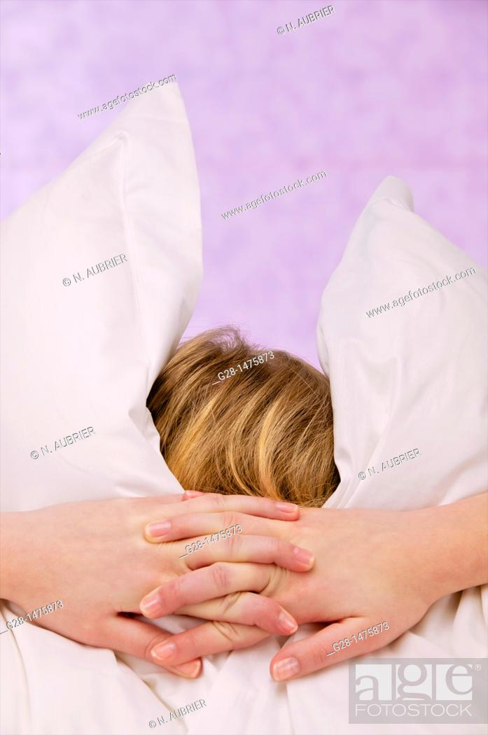 Stock Photo: Concept : young woman burrying herself in her pillows because of overstress or fear, depression, or desire to cut herself from the world around.