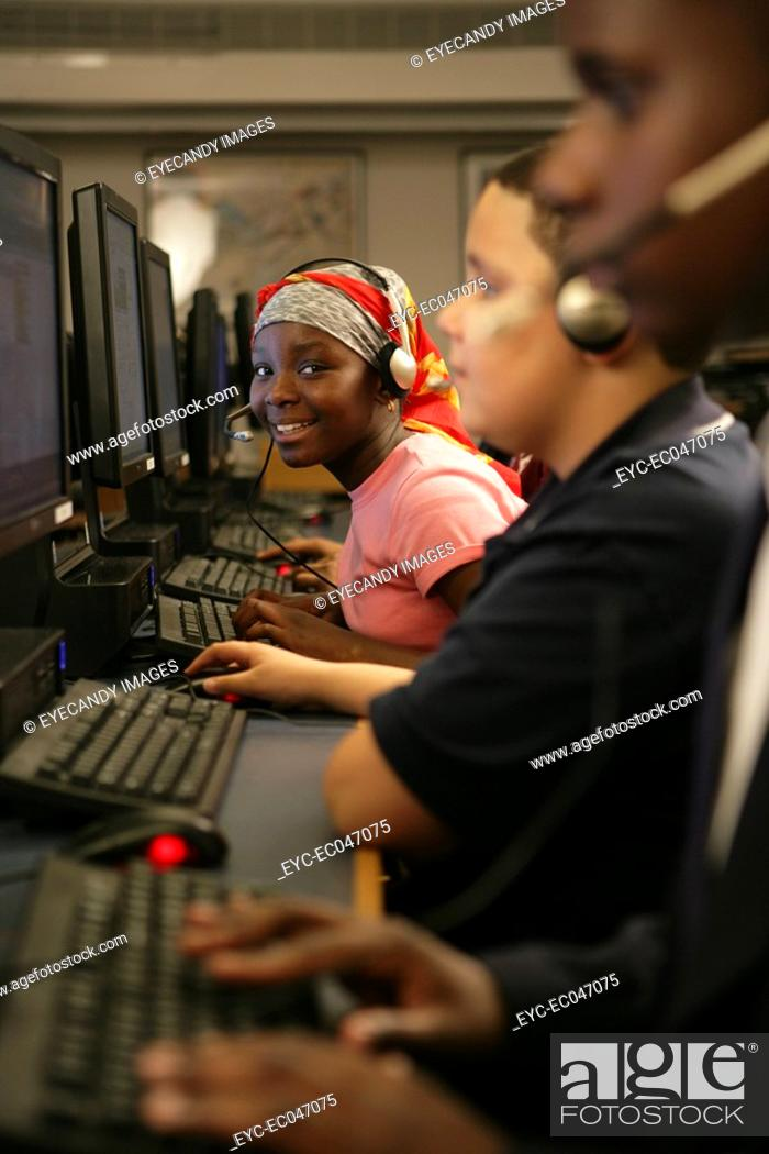 Stock Photo: Girl and boys 11-12 operating computers.