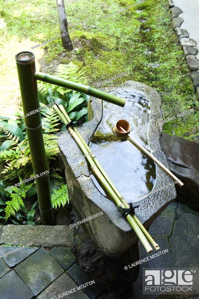 Stock Photo: Stone water fountain with bamboo spigot and ladle.