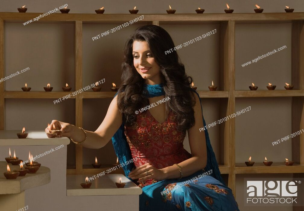 Stock Photo: Woman decorating oil lamps in Diwali festival.