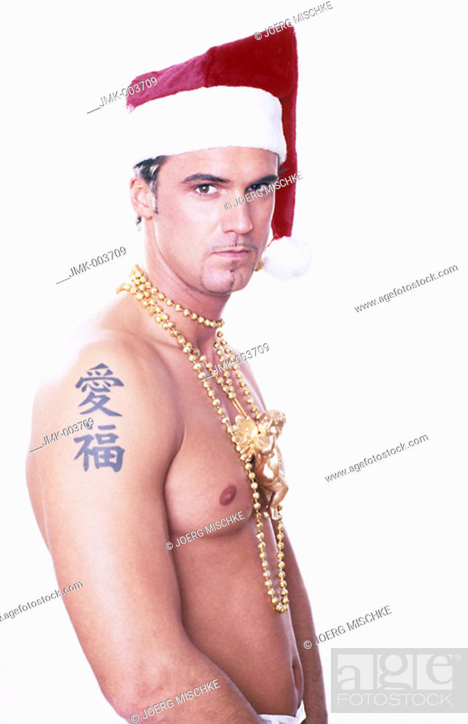 Stock Photo: A young man, 20-25 25-30 30-35 years old, stripped to the waist, wearing a Santa Claus cap and a golden necklace.